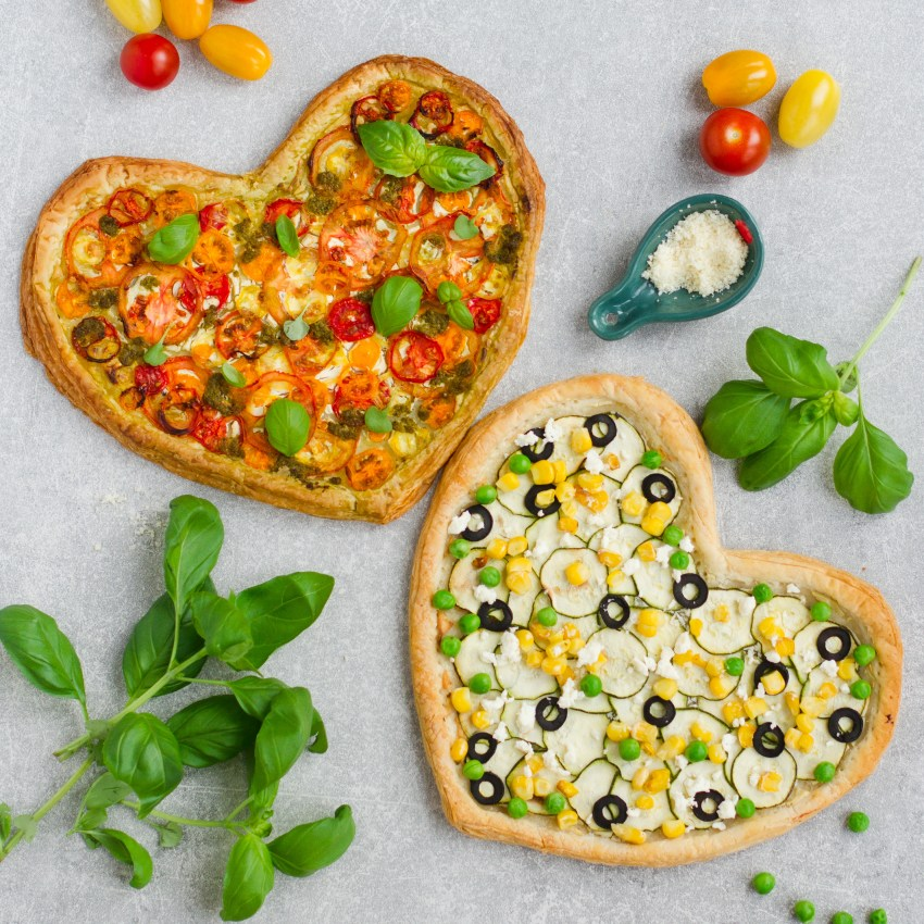Vegetarian vegan valentines puff pastry pizzas with rainbow tomatoes and courgette, olives, sweetcorn, peas and feta