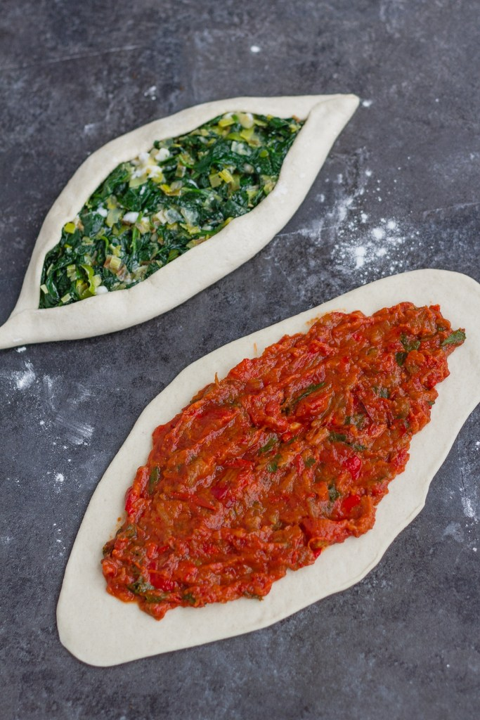 Spinach, leek & vegan feta Vegan Turkish pide, folded before baking plus pide with aubergine, tomato and red pepper mixture