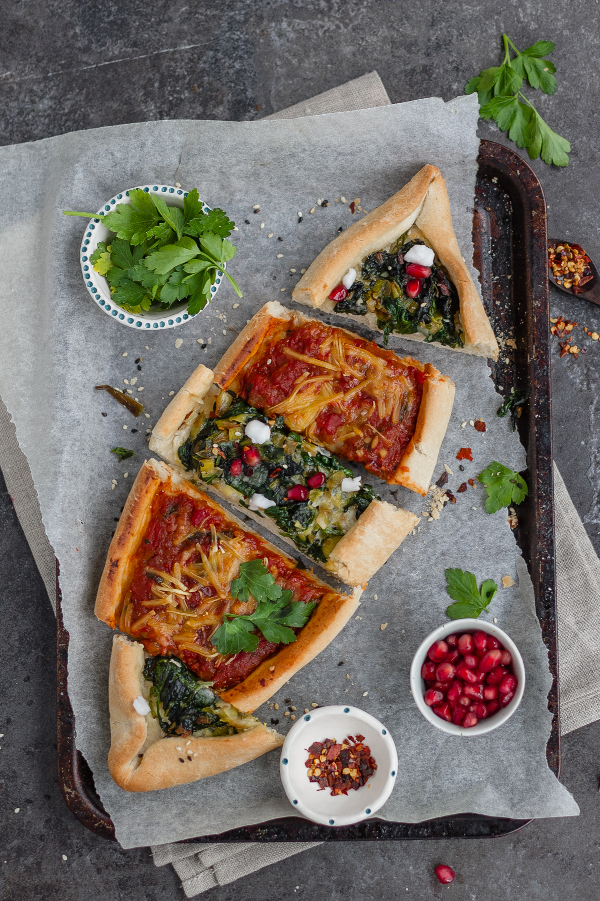 combination of two vegan pide (turkish flat bread) including spinach, leek and vegan feta plus aubergine, tomato and red peper. Toppings in small bowl include pomegranate, chilli flaked and parsley