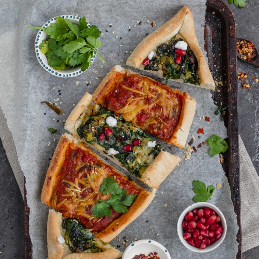 combination of two vegan pide including spinach, leek and vegan feta plus aubergine, tomato and red peper. Toppings in small bowl include pomegranate, chilli flaked and parsley
