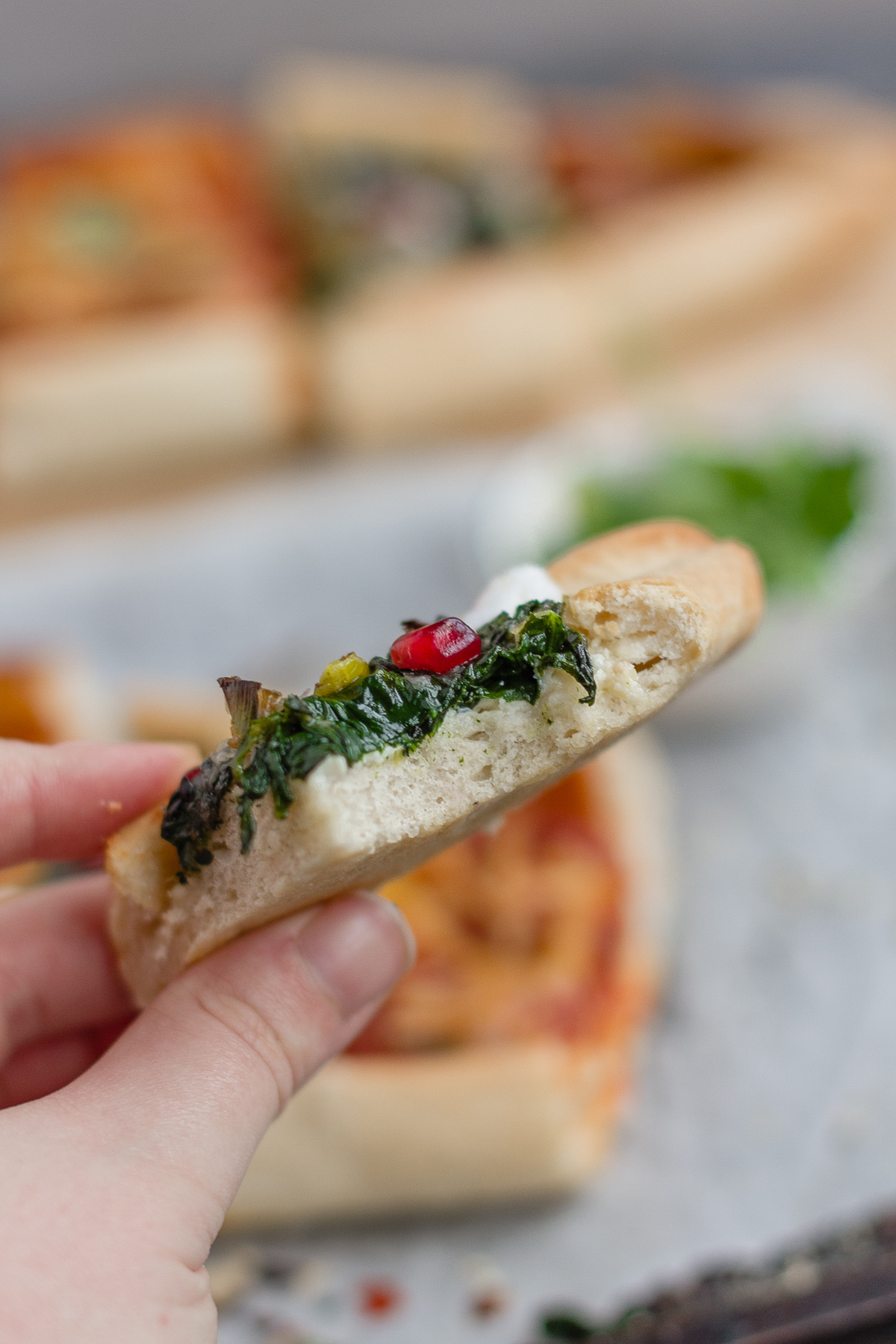 holding slice of vegan pide up