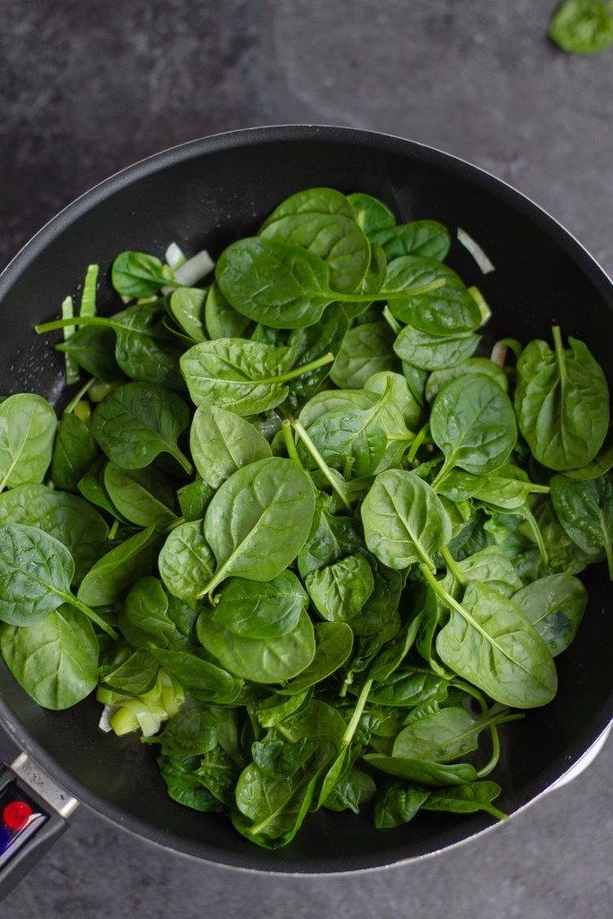 adding spinach to the frying pan with the leek