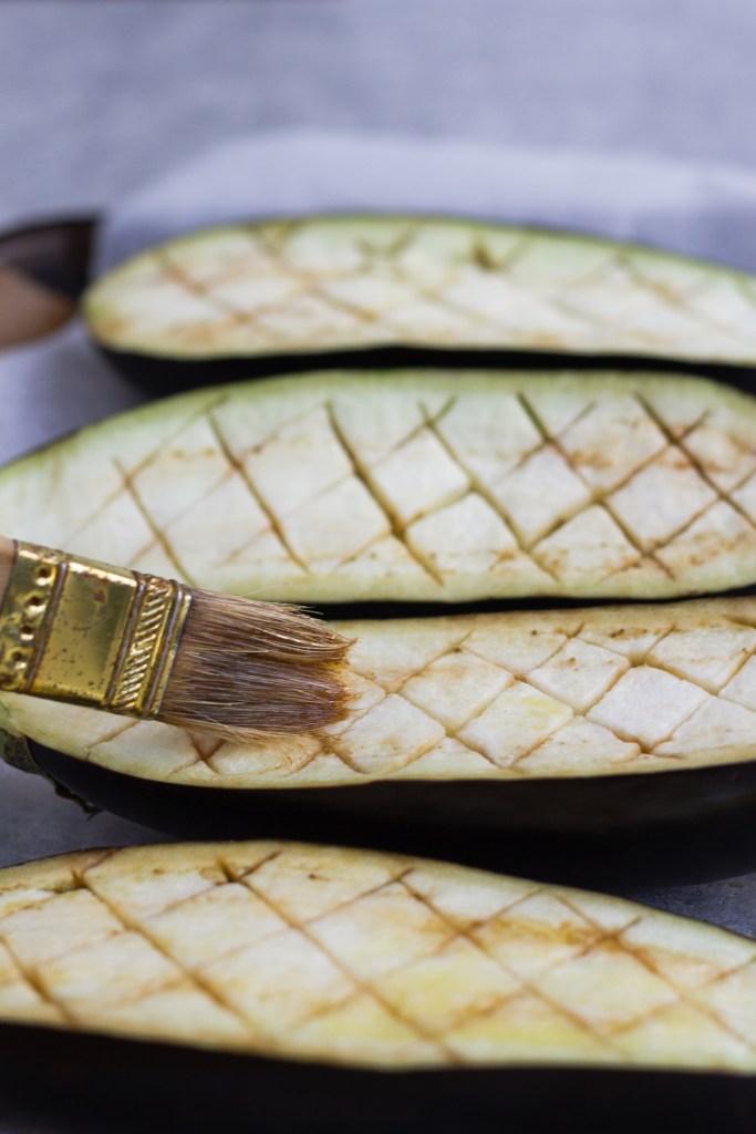 brushing scored eggplant with olive oil