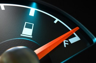 A closeup of a backlit illuminated gas gage with the needle indicating a near full tank on an isolated dark background