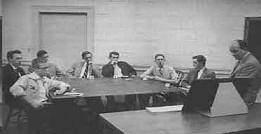 An example of Asch's experimental procedure in 1955. There are six confederates and one real participant (second to last person sitting to the right of the table).
