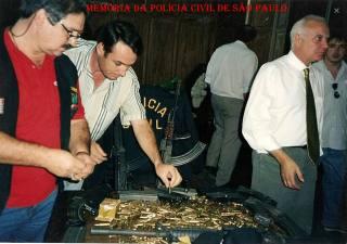 No ano de 2.000, o então Delegado Seccional de Campinas Djahy Tucci Junior; e os Investigadores José Antonio (de vermelho) e Jair (de branco), em apreensão de armamento pesado, quando da prisão de membros da família Oliveira. ( Acervo do Policial Civil Adriano Barros).