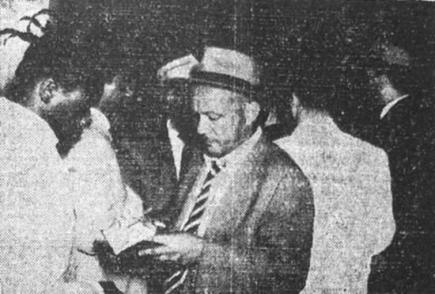 nvestigador Casimiro, da Polícia Civil de Santos, verificando documento durante batida policial nos anos 50.