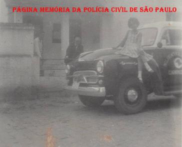 Delegado Coriolano Nogueira Cobra defronte sua residência e sua filha Teresa Cobra sentada no paralama de uma viatura, ano 61 ou 62.