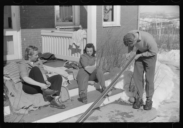 Skiers on porch of Mr. Dickinsons home in Lisbon, Franconia, New Hampshire. He installed a ski tow on his property three years ago costing around one thousand dollars, and this is the first year he has made any money on it, but business is increasing rapidly now. He has a small dairy farm and until the hurricane last year destroyed his entire grove of maple trees, he made and sold maple syrup.  (March 1939 or 1940)