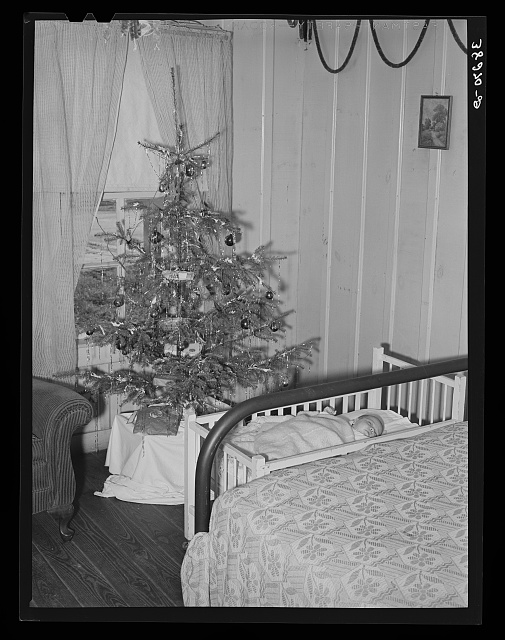 Baby and Christmas tree in corner of living room in home of construction workman. This family came to Corpus Christi from northwest Texas eight months ago.  December 1940