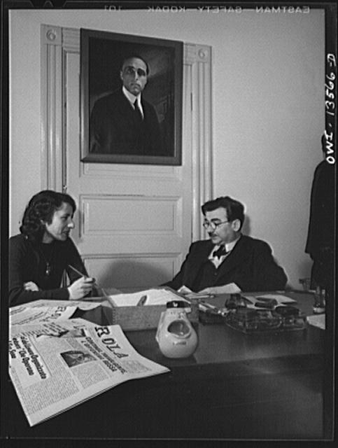 New York, New York. Girolamo Valente, editor of the progressive Italian weekly, La Parola, conferring with his secretary. The ashtray in the form of open-mouthed Mussolini was presented by a friend. Painting on the wall is of Giacomo Matteotti, an Italian patriot. Valente is a prominent anti-fascist in this country.  1943 January.  (Photo: Marjory Collins)
