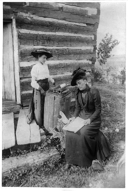 Picture of Mrs. Norah Gridley, cousin of Mrs. Abraham Lincoln, and Miss May Coleman, the typewriter, taken outside of and near the corner of the Lincoln Cabin in Illinois that was built by Thomas Lincoln and visited by his son, Abraham Lincoln.  August 9, 1891.