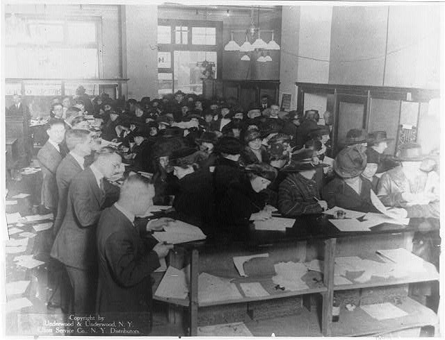 Everybodys doing it, Doing what? Paying taxes, of course  Large group of people filling out tax forms in Internal Revenue office. (c1920)