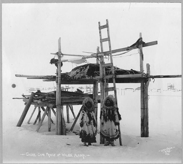 Eskimo women and storage place.  Photo by Lomen Bros., Nome, 1916.