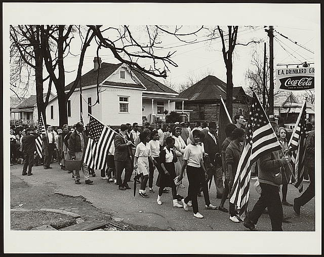 Participants, some carrying American flags, marching in the civil rights march from Selma to Montgomery, Alabama in 1965