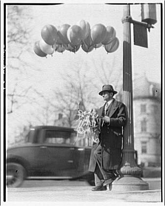 Balloon man leaning against post. c1920/1950.  Theodor Horydczak, photographer. (Library of Congress)