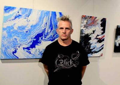 Artist Paul Coté in front of a display of his work at the Driftwood IV Art Gala.