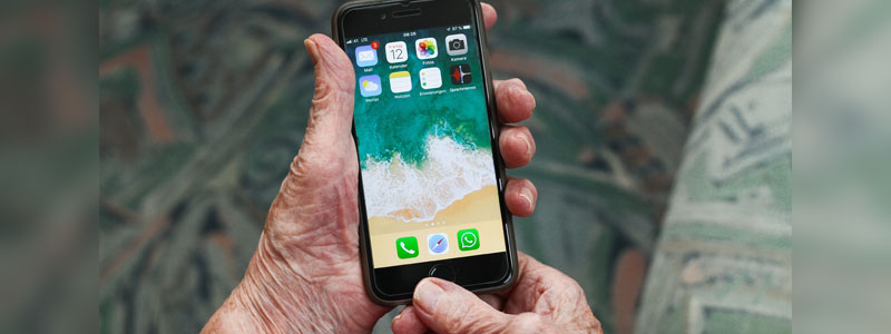 Older person's hands holding smartphone