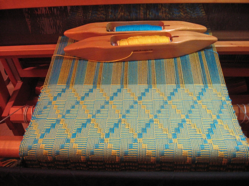 Using two shuttles of alternating colors, the weaving has begun to show the design of the shadow weave pattern.