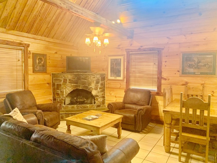 Living room with stone fireplace and vaulted ceilings in rustic cabin
