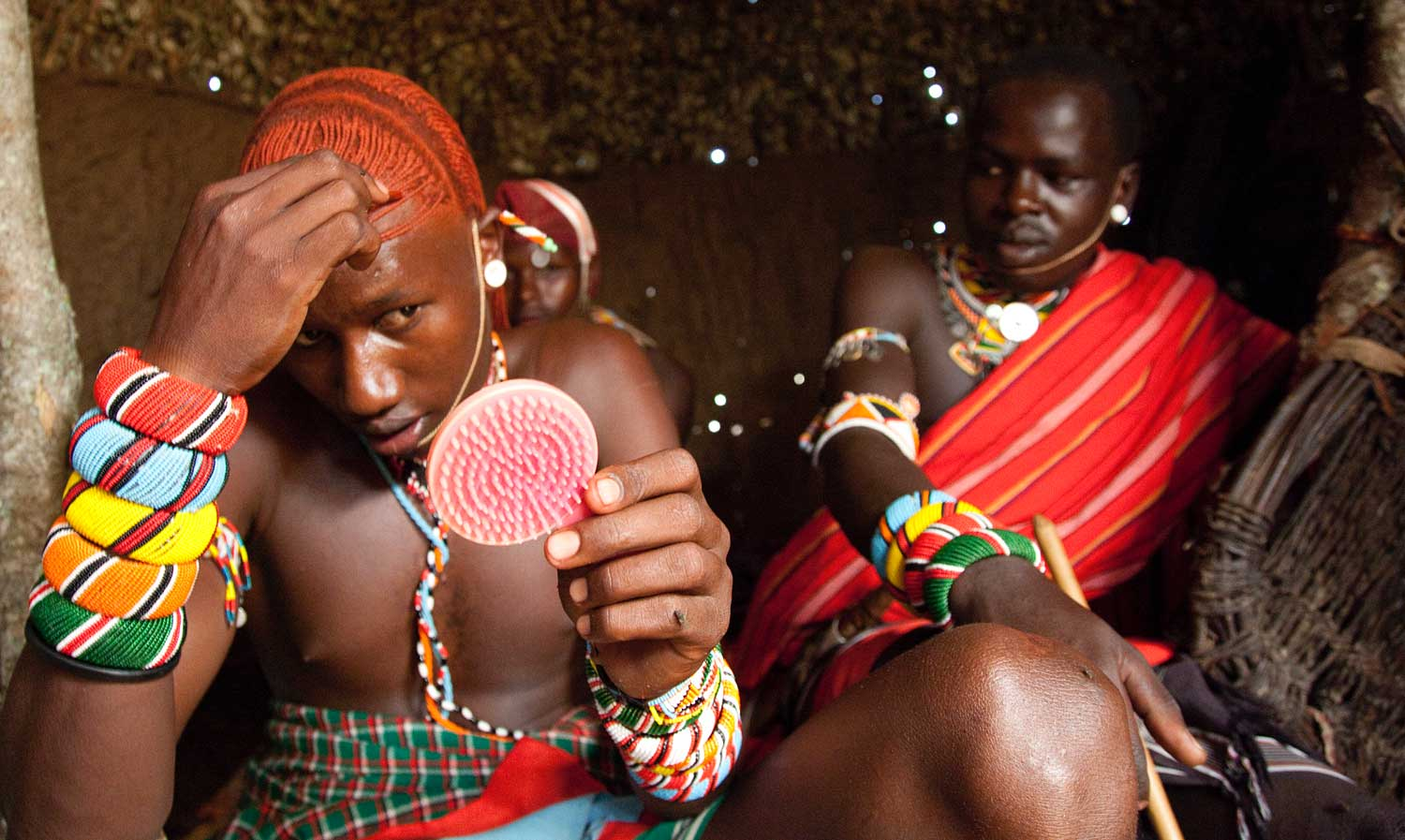 Marcy Mendelson, The Samburu Story | Never without a pocket mirror, the moran's appearance takes a great amount of skill and maintenance.  His natural long hair is carefully twisted and covered in ochre.