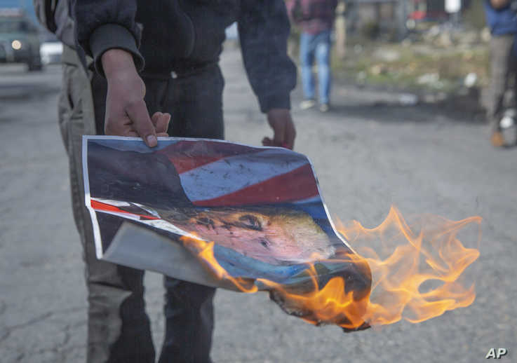 A Palestinian protester burns a poster with a picture of U.S. President Trump during minor clashes in the West Bank city of…
