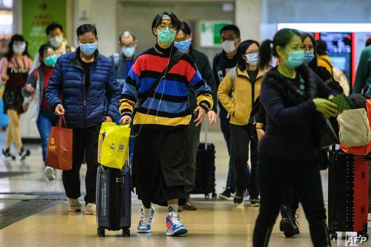 Passengers protective wear face masks as they arrive from Shenzhen to Hong Kong at Lo Wu MTR station hours before the closing…