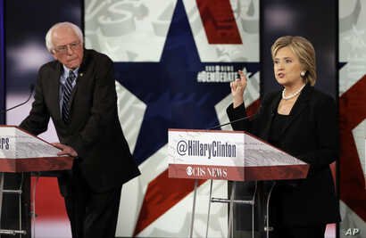 FILE - Hillary Rodham Clinton, right, makes a point as Bernie Sanders listens during a Democratic presidential primary debate in Des Moines, Iowa, Nov. 15, 2015.