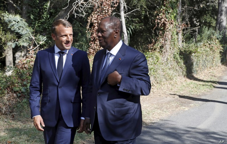 French President Emmanuel Macron, left, talks with Ivory Coast's President Alassane Ouattara during a ceremony marking the 75th anniversary of the WWII Allied landings in Provence, in Saint-Raphael, southern France, Thursday, Aug. 15, 2019. Starting…