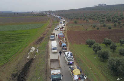 Civilians flee from Idlib to find safety inside Syria near the border with Turkey, Tuesday, Feb. 11, 2020.  Syrian opposition…
