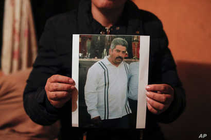 Rebeca Valencia Gonzalez holds up a picture of her husband, environmental activist Homero Gomez Gonzalez, in their home in…