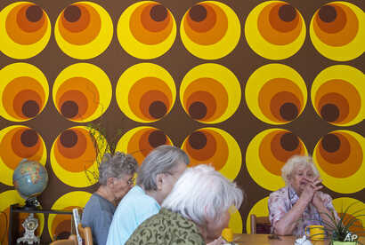 In this May 17, 2017 photo residents sit in front of a colorful wallpaper of the 70s in the Alexa Seniors' Residence in Dresden…