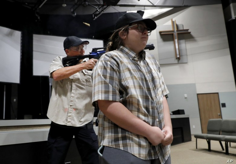 Brett Faulkner, left, fires blanks out of an assault rifle as he and Julia Gant, right, participate in a hostage-taking scenario during a security training session at Fellowship of the Parks campus in Haslet, Texas, July 21, 2019.