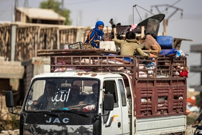 Displaced Syrians sit in the back of a pick up truck as Arab and Kurdish civilians flee amid Turkey's military assault on…