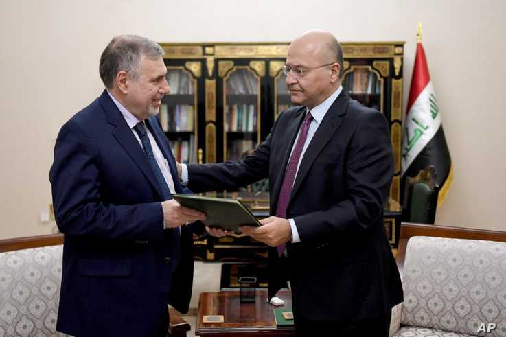 Iraqi President Barham Salih, right, instructs newly appointed Prime Minister Mohammed Allawi in Baghdad, Iraq, Saturday, Feb…