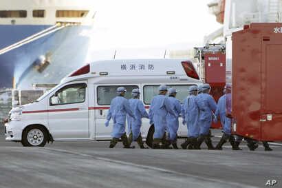 Members of Japan Self Defense Forces walk into the quarantined cruise ship Diamond Princess in the Yokohama Port, Feb. 9, 2020, in Yokohama, Japan.
