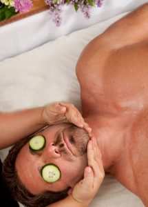 Cucumber on man's eyes to remove fine lines