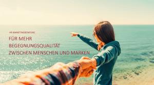 Titelbild, junge Frau an einer Küste, hält einen Mann am Arm und deutet über das offene Meer zum Horizont