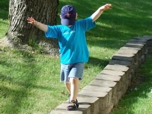 Balans oefenen door over een muurtje te lopen