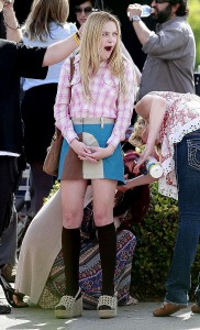 Actor Dakota Fanning waits while an assistant cleans her legs.