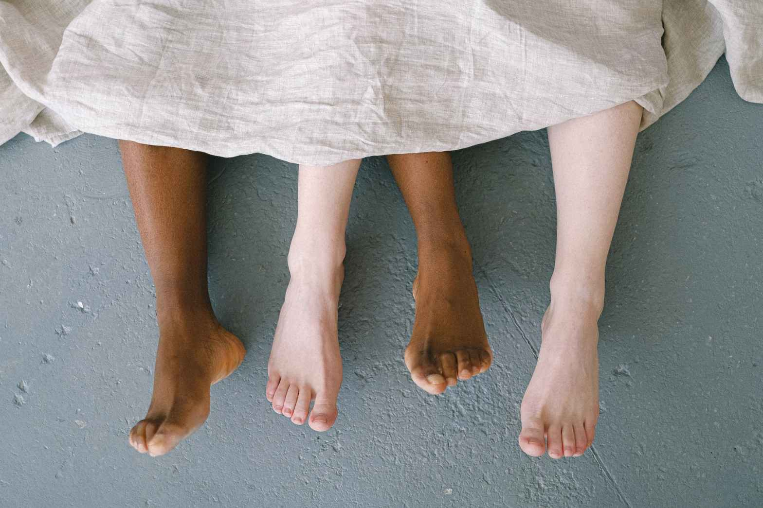bare feet coming out of bed sheets