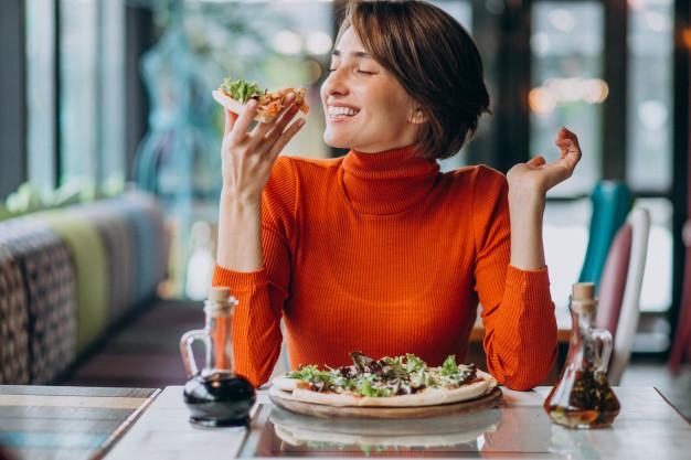 femme savoure une pizza