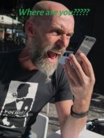 Man with bald head and s beard, wearing a black t-shirt shouting into his mobile phone