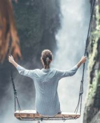 Coloured photo of woman on a giant swing in front of a waterfall