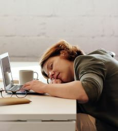 Coloured image of female asleep at her desk