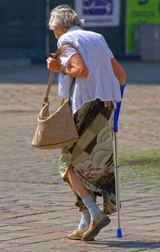 Coloured image of elderly lady walking with walking stick