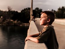 Young boy leaning on bridge just staring out