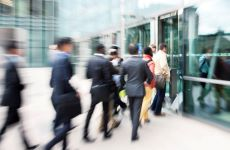 Blurred colour image people dashing through glass doors