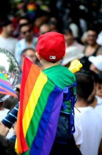 Colour image of little boy wearing LGBT Rainbow flag, sitting on someones shoulders
