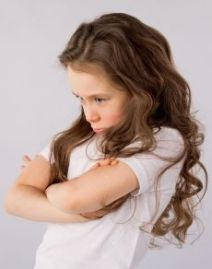 Coloured image of young girl with long auburn hair, face scrunched uo, arms crossed - looking grumpy